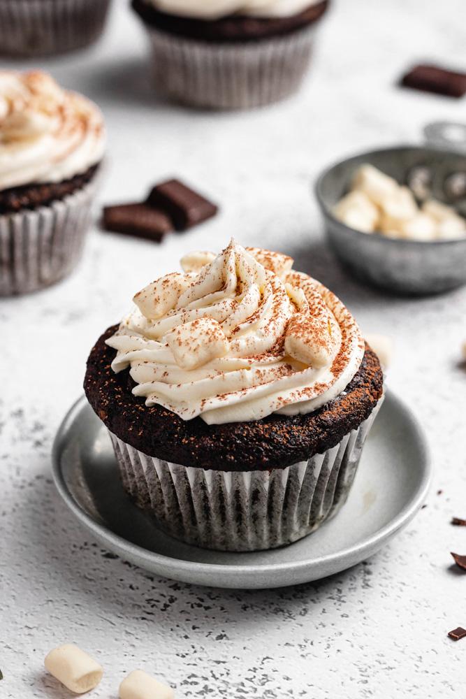 Veganský čokoládový cupcake s máslovým krémem na talířku posypaný kakaem