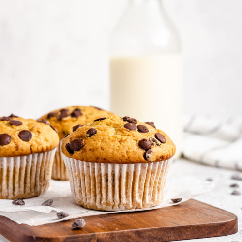 Three Bakery-Style Chocolate Chips Muffins On Wooden Board