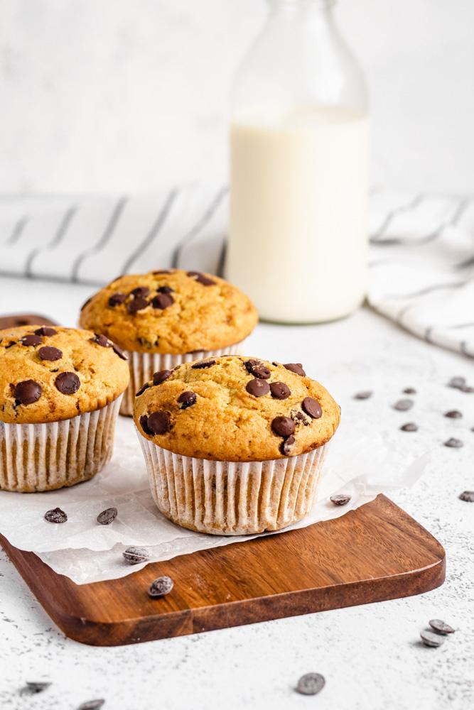 Tři muffiny na desce v pozadí s lahví mandlového mléka