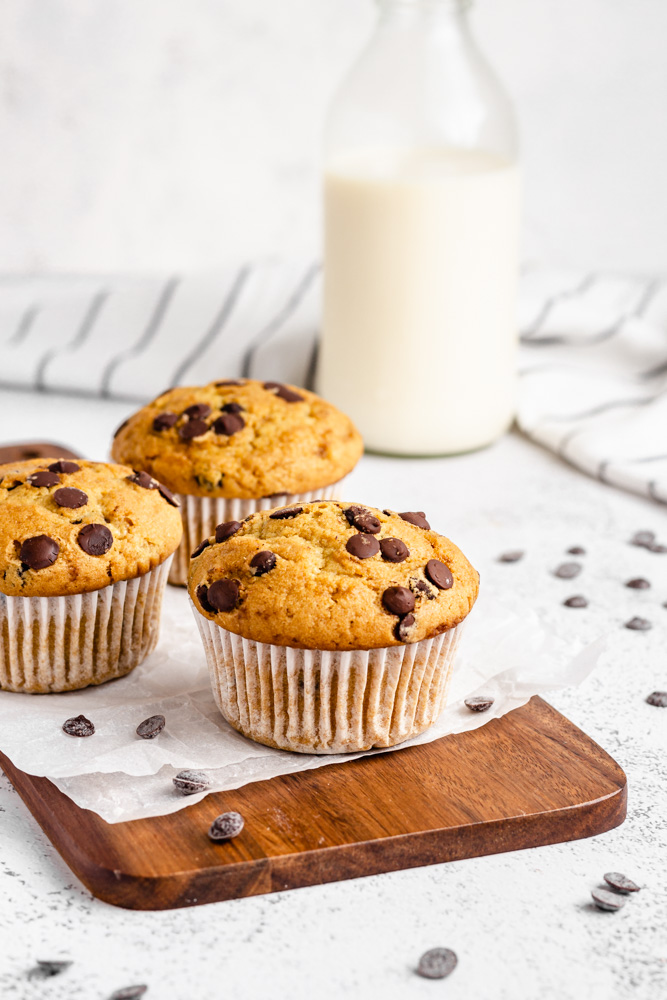 Three Chocolate Chip Muffins On Wooden Board