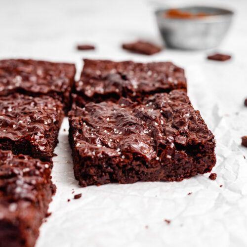 Vegan Brownies With Shiny Crackly Top On White Parchment Paper