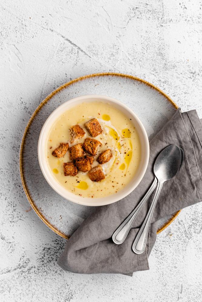 Bramborová polévka v misce položené na talíři, s ubrouskem a lžícemi