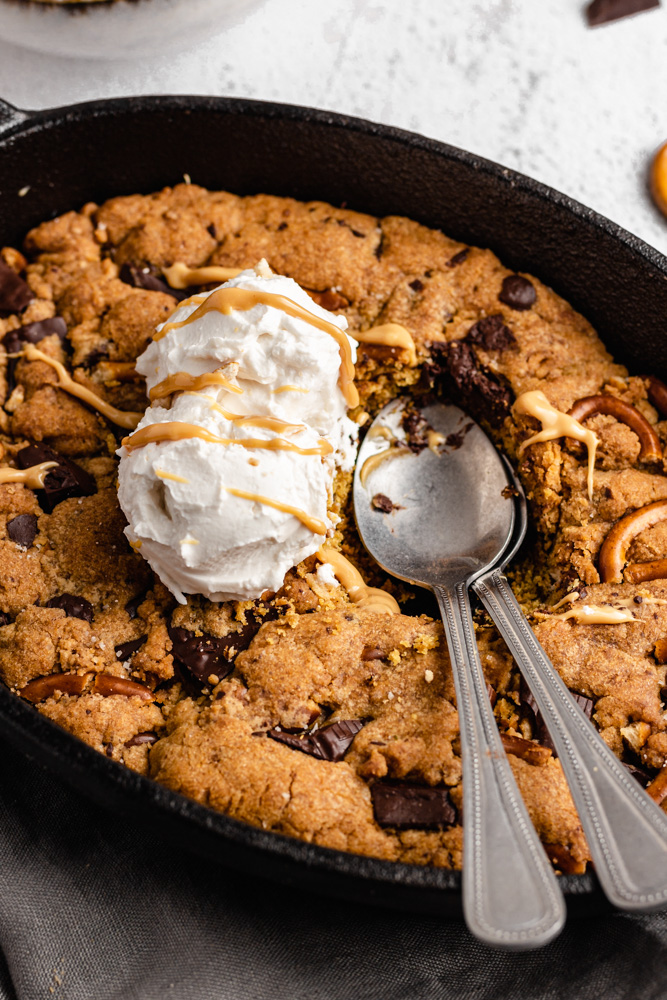 Close Up Of Chocolate Chunk Skillet Cookie Topped With Ice Cream, With Two Spoon