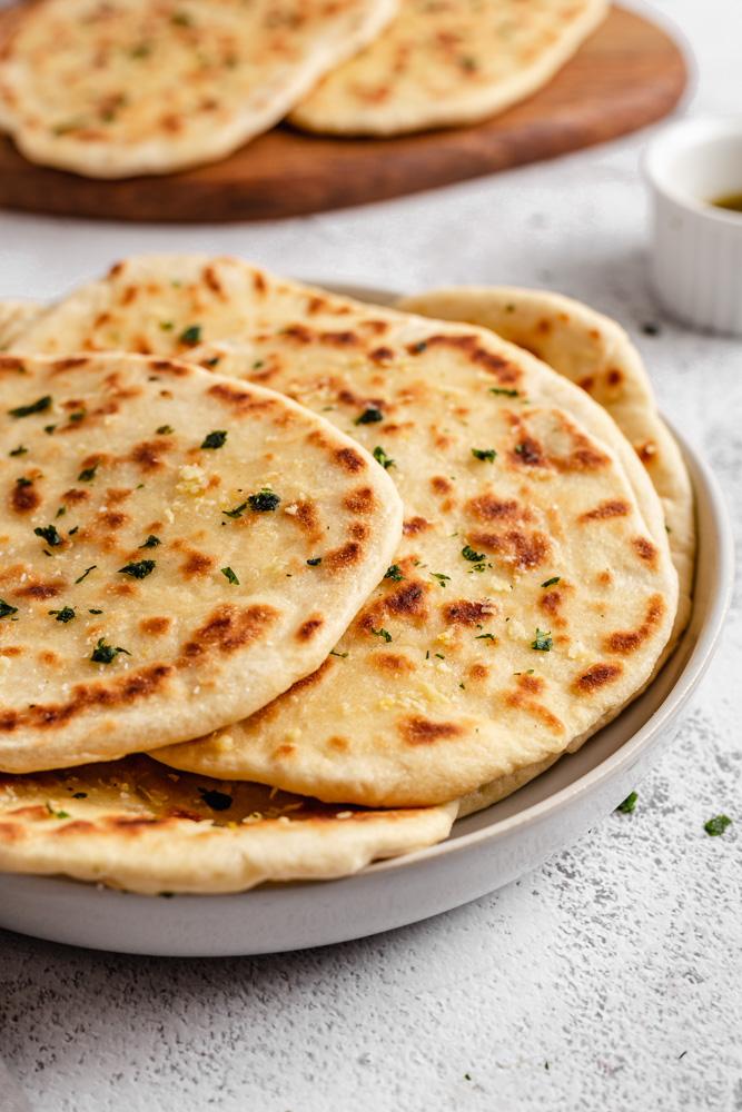 Indický chléb naan podávaný s česnekovým máslem