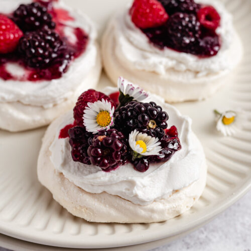 Mini pavlovas topped with berries on a plate