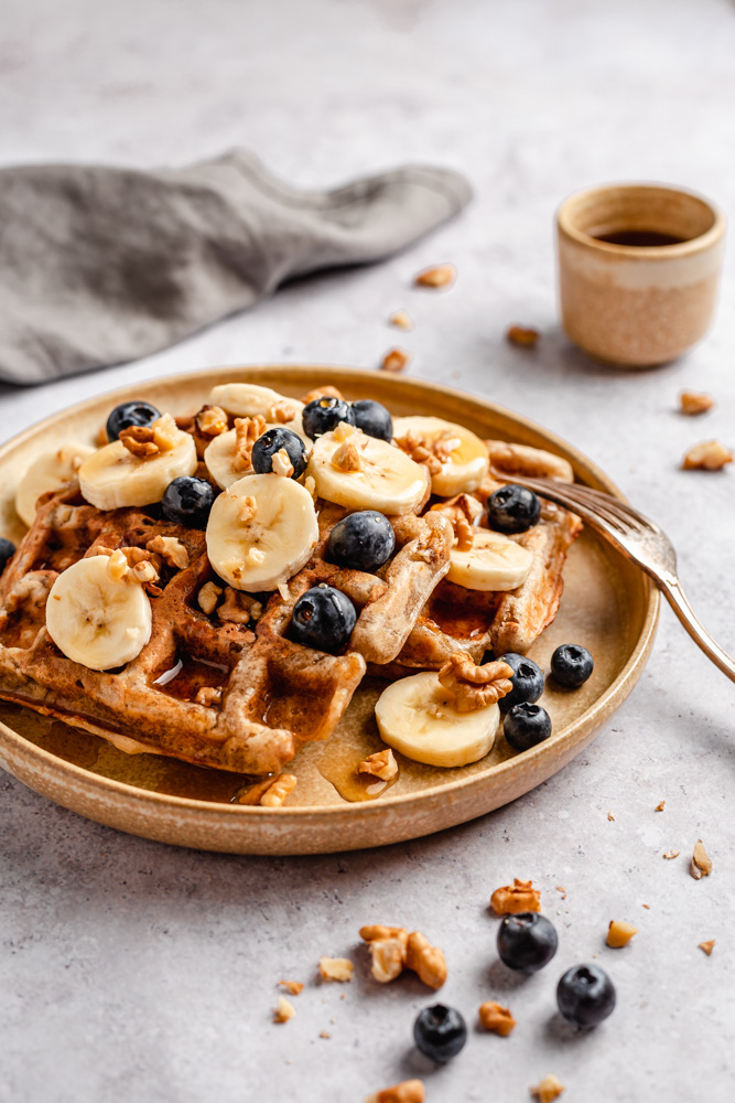Banana waffles served with sliced banana, blueberries, chopped walnuts, and maple syrup