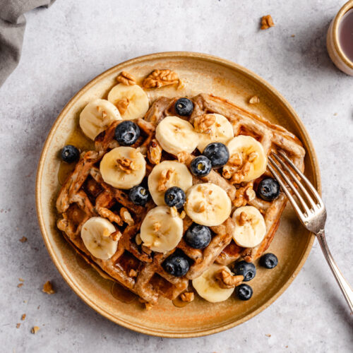 Headshot of waffles topped with bananas, blueberries, walnuts, and maple syrup