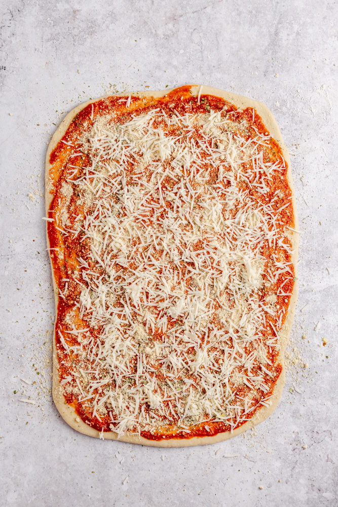 Rolled out dough with tomato sauce, vegan mozzarella, cashew parmesan and Italian herbs