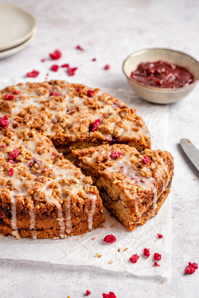 Raspberry cake with streusel topping drizzled with glaze